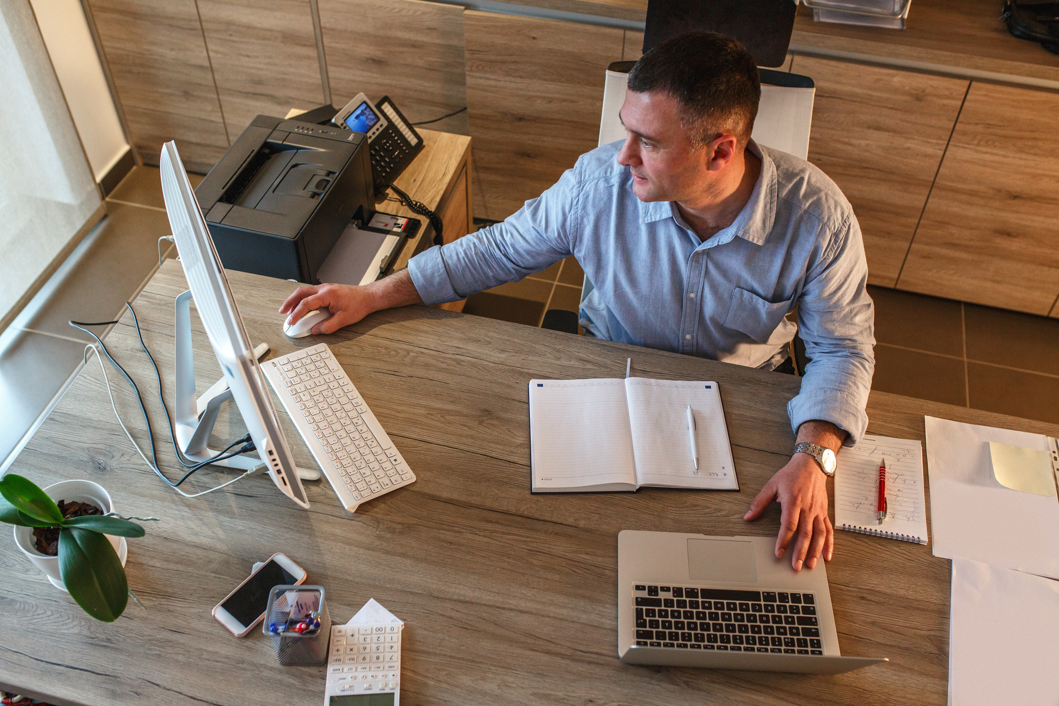A man sitting at an office desk and working on a computer with a notepad and pen in front of him
